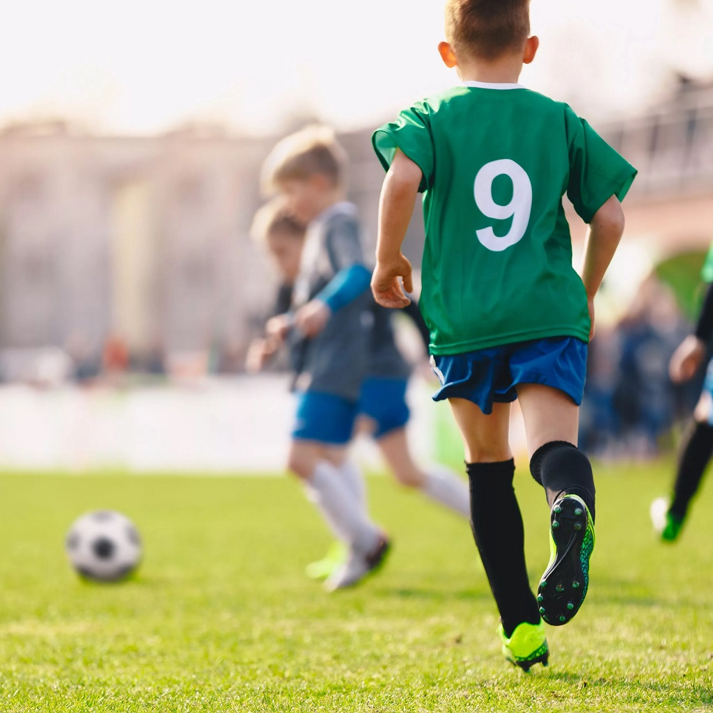child playing football in green shirt